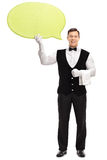 Male waiter holding a speech bubble. Full length vertical shot of a young male waiter holding a big yellow speech bubble isolated on white background Stock Photo