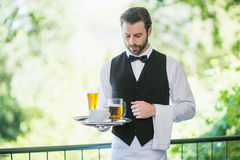 Male waiter holding tray with beer glass and coffee cup in restaurant Royalty Free Stock Photos