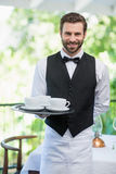 Male waiter holding tray with coffee cups Stock Photography