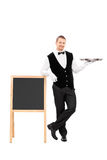 Male waiter holding a tray and leaning on a blackboard. Full length portrait of a male waiter holding an empty tray and leaning on a blackboard isolated on white Stock Photos