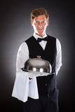 Male Waiter Holding Tray And Lid. Portrait Of A Male Waiter Holding Tray And Lid Over Black Background Stock Photography