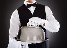 Male waiter holding tray and lid Stock Photo