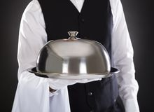 Male waiter holding tray and lid. Portrait Of A Male Waiter Holding Tray And Lid Over Black Background Stock Photos