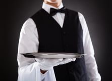 Male waiter holding tray. Portrait Of A Male Waiter Holding Tray Over Black Background Stock Images