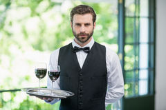 Male waiter holding tray with wine glasses Royalty Free Stock Images