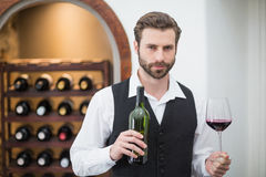Male waiter holding wine glass and wine bottle in the restaurant Stock Photo