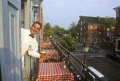 Male waiter outside red-checked tables at outdoor Fish Market restaurant in Alexandria, VA Stock Images