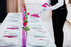 Male Waiter Placing Napkin. On Wedding Table Royalty Free Stock Image