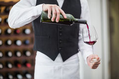 Male waiter pouring wine in wine glass. Mid-section of male waiter pouring wine in wine glass Royalty Free Stock Photos