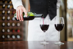 Male waiter pouring wine in wine glasses Stock Images
