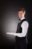 Male Waiter Presenting Something. Portrait Of A Male Waiter Presenting Something Over Black Background Royalty Free Stock Images
