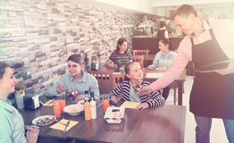 Male waiter serving cheerful family in family cafe. Male waiter serving cheerful family in comfy family cafe Royalty Free Stock Photography