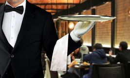 Male waiter serving in restaurant with people dining in background. Male waiter serving in restaurant with blur image of people dining in background Royalty Free Stock Images