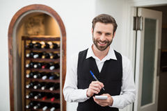 Male waiter smiling while taking down order Royalty Free Stock Photos