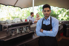 Male waiter standing with arms crossed in the restaurant. Portrait of male waiter standing with arms crossed in the restaurant Royalty Free Stock Image