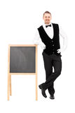 Male waiter standing next to a blackboard. Full length portrait of a male waiter standing next to a blackboard isolated on white background Stock Photo