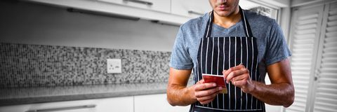 Composite image of male waiter taking order. Male waiter taking order against counters in stylish kitchen Stock Photography