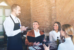 Male waiter taking order from visitors. Diligent friendly male waiter taking order from visitors in country restaurant Stock Photography