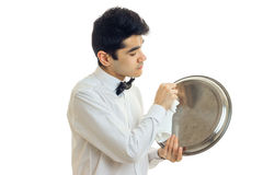 Male waiter in uniform with bowtie cleans a trey. Isolated on white background Stock Photography