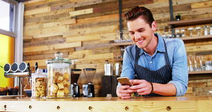 Male waiter using mobile phone at counter stock footage