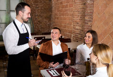 Male waiter writing down order. Cheerful male waiter writing down order from visitors in country restaurant Royalty Free Stock Images