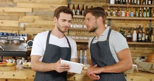 Male waiters discussing over digital tablet 4k