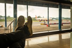 Male waiting for her flight. The passenger sits at the airport with his leg folded against the background of aircraft on the runway Stock Photography