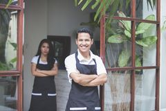 Male waitress standing with arms crossed in cafe Stock Photography