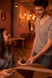 Male waitron serving tea to girl. Young male waitron serving a cup of tea to a lovely young lady in a restaurant while she looks at him with a toothy smile Stock Photos
