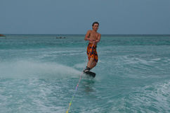 Male Wakeboarding Off the Coast of Aruba. Young male wakeboarding off the coast of Aruba Royalty Free Stock Image