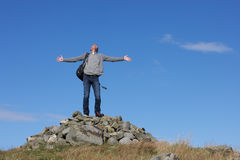 Male Walker Standing On Pile Of Rocks. With Arms Outstretched Stock Photo