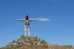 Male Walker Standing On Pile Of Rocks. With His Arms Outstretched Royalty Free Stock Photography