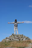 Male Walker Standing On Pile Of Rocks. With His Arms Outstretched Stock Photo