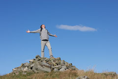 Male Walker Standing On Pile Of Rocks. With His Arms Outstretched Royalty Free Stock Images