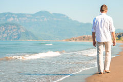 Male walking barefoot on the beach Stock Image
