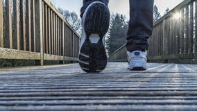 Male walking on a bridge. Young male legs with sneakers walking on bridge Royalty Free Stock Images