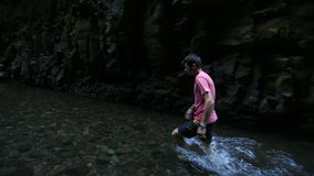 Male Walking Through Creek stock footage