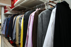 Male wardrobe. Home interior with male clothing hanging on Stock Images