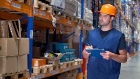 A male warehouse inspector makes clipboard notes while turning corners. 4K. stock video footage