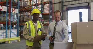 Male warehouse manager and warehouse worker in loading bay 4k stock video footage