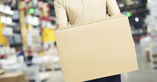 Male warehouse worker carrying a carton box. Of goods in a cash & carry wholesale store Stock Photos