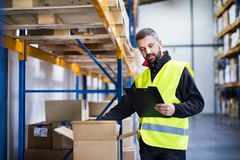 Male warehouse worker with clipboard controlling stock. Young male warehouse worker with clipboard controlling stock Stock Photography