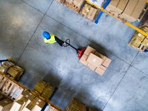 Male warehouse worker pulling a pallet truck. Young male warehouse worker pulling a pallet truck with boxes. Aerial view Stock Photo