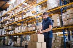 Free Male Warehouse Worker Sealing Cardboard Boxes. Royalty Free Stock Photo - 108248365
