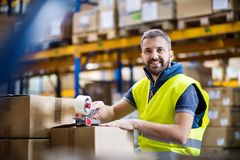 Male warehouse worker sealing cardboard boxes. Male warehouse worker sealing cardboard boxes, smiling stock images