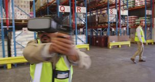 Male warehouse worker using VR headset and controller in loading bay 4k stock video