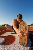 Male warmup. A male athlete stretching at the race track Stock Images