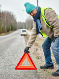 Male and warning triangle. Mid adult man wearing reflector vest and he have a red warning triangle - road and vehicle on background Stock Photo