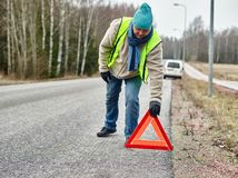 Male and warning triangle. Mid adult man wearing reflector vest and he have a red warning triangle - road and vehicle on background Royalty Free Stock Photo