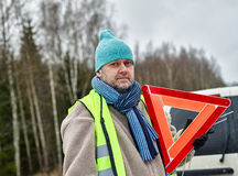 Male and warning triangle. Mid adult man wearing reflector vest and he have a red warning triangle - vehicle on background Stock Photography